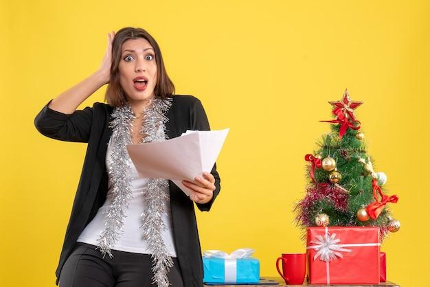 Ambiance de noël avec une belle dame surprise émotionnelle debout dans le bureau et tenant des documents au bureau sur jaune