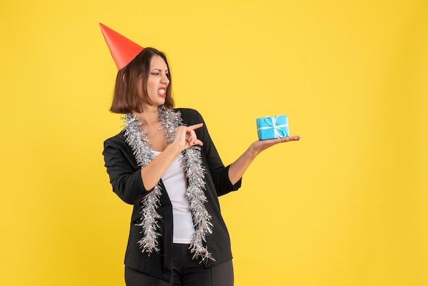 Ambiance de noël avec une femme d'affaires sérieuse en costume avec un chapeau de noël et tenant un cadeau sur jaune