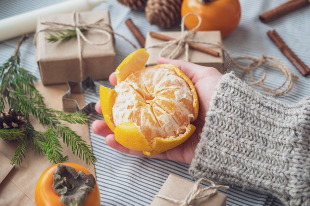 Ambiance de noël, fille nettoyant la mandarine parmi les cadeaux et les arbres de noël, vue de dessus, gros plan. fond du nouvel an, mandarine dans les mains des femmes. emballage de cadeaux à partir de matériaux naturels.
