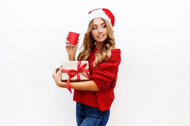 Ambiance de nouvel an ou de réveillon de noël. jolie fille blonde en chapeau de mascarade tenant des coffrets cadeaux humeur joyeuse.