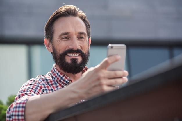 Ambiance numérique. joyeux bel homme à l'aide de son téléphone alors qu'il était assis sur le banc