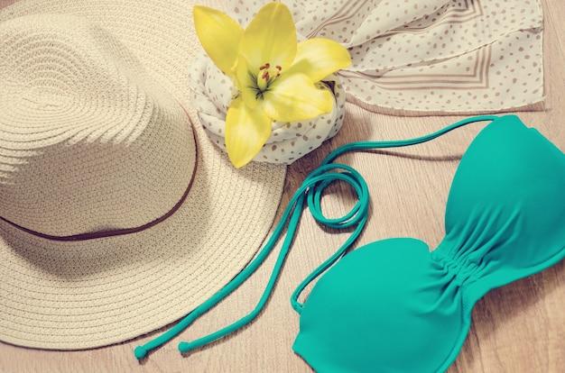 Ambiance pour les vacances ou les voyages - chapeau de paille, maillot de bain, écharpe et fleur jaune