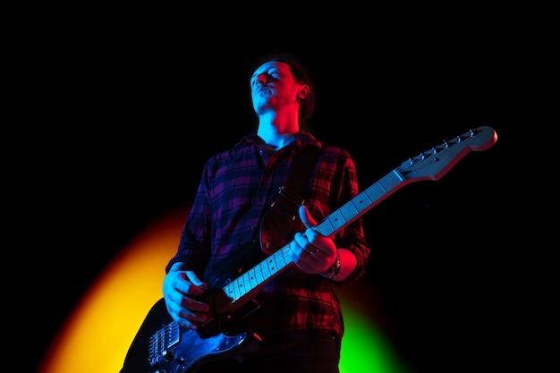 Ambiance sombre jeune guitariste musicien inspiré et expressif se produisant sur dégradé de couleur