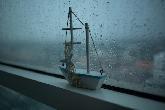 Ambiance triste d'une pièce avec pluie dehors.