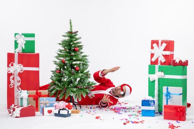Ambiance de vacances festives avec le père noël couché derrière l'arbre de noël près de cadeaux sur fond blanc