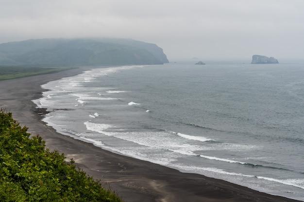 Ambiance venteuse et surf contre ciel sombre avant l'arrivée de la tempête.