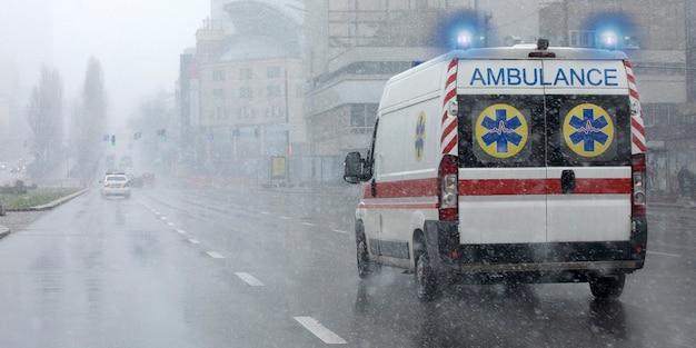Une ambulance a emmené le patient à la clinique avec les clignotants allumés. mauvais temps à l'extérieur, pluie avec neige mouillée.