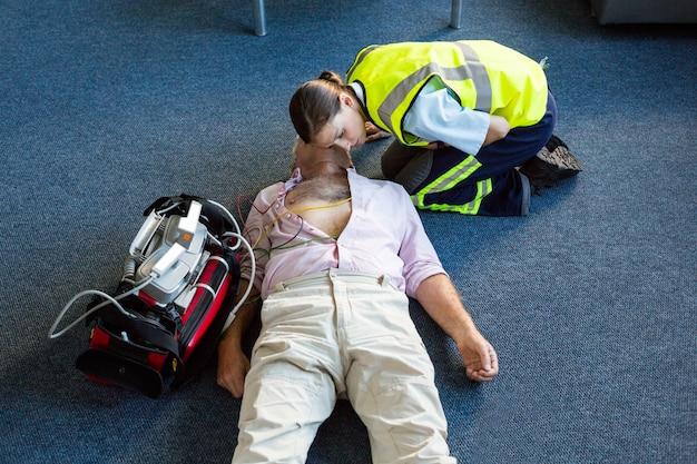 Ambulancier féminin pendant la formation de réanimation cardio-pulmonaire