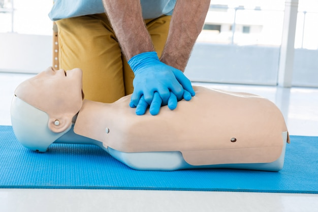 Ambulancier pratiquant la réanimation cardio-pulmonaire sur mannequin