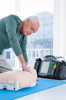 Ambulancier pratiquant la réanimation sur mannequin