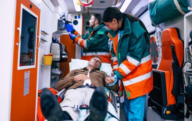 Les ambulanciers paramédicaux travaillent avec un patient âgé alors qu'il se trouve sur une civière dans une ambulance.