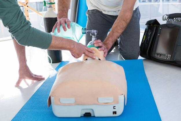 Ambulanciers pratiquant la réanimation cardio-pulmonaire sur mannequin