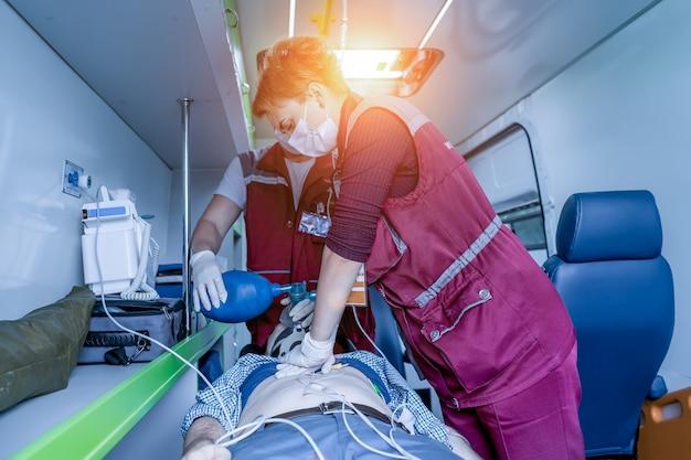 Les ambulanciers réaniment le patient dans la voiture.