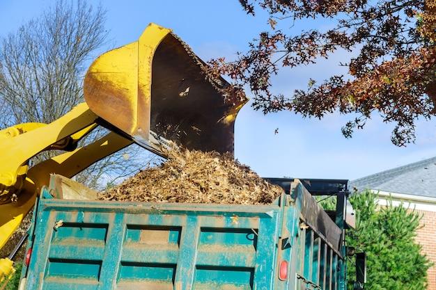 Amélioration de la ville sur le nettoyage des feuilles d'automne dans le travail d'équipe avec un tracteur feuilles tombées dans la voiture