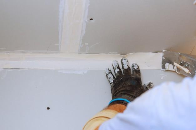 Améliorations de la maison. mettre du plâtre sur le mur avec une spatule