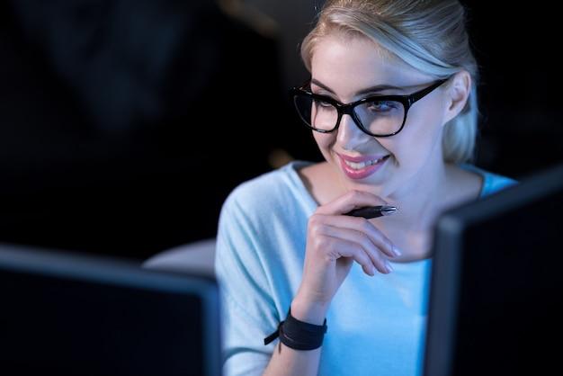 Améliorer mes compétences. souriant charmant programmeur confiant assis au bureau et utilisant des ordinateurs tout en travaillant sur la résolution des codes de mot de passe