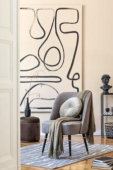 Aménagement intérieur du salon avec fauteuil gris élégant, peintures abstraites au mur, fleurs dans un vase, oreiller, plaid et accessoires personnels élégants. notion beige. home staging moderne.