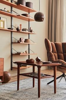 Aménagement intérieur du salon avec fauteuil marron, table basse, étagère en bois, livre, cadre photo, décoration et accessoires personnels élégants dans la décoration intérieure.