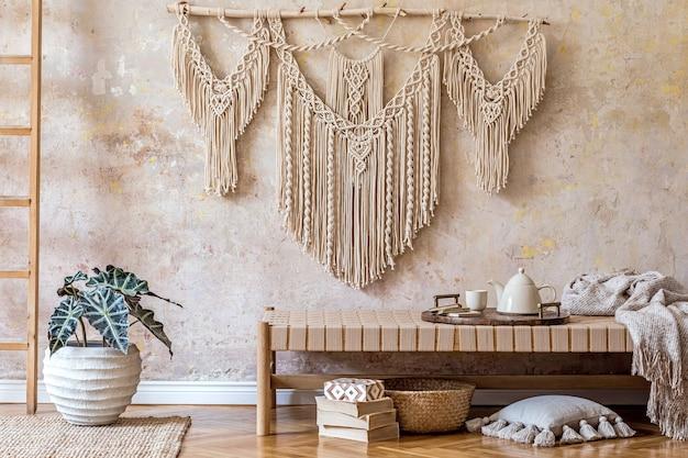 Aménagement intérieur d'un salon élégant avec chaise longue beige, oreillers, lanterne, macramé, fleur séchée, théière sur le plateau, décoration et accessoires personnels élégants dans un concept oriental.