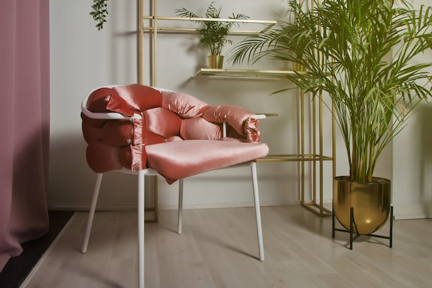 Aménagement intérieur d'un salon de réception de luxe avec une élégante chaise rose, de nombreuses plantes et des accessoires élégants sur une étagère et une étagère. décor de maison ou de travail moderne et élégant. espace copyright pour le site