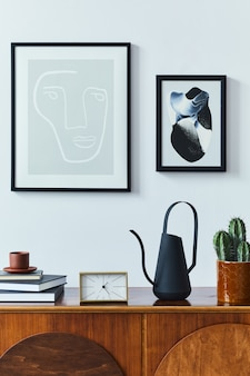 Aménagement intérieur d'un salon scandinave avec commode en bois élégante, cadres d'affiches maquettes, livre, horloge, bidon d'eau, décoration, cactus et accessoires personnels dans un décor rétro