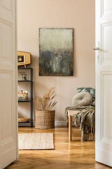 Aménagement intérieur d'un salon de style oriental avec chaise longue moderne, étagère, panier en rotin, radio rétro, fleurs et accessoires personnels élégants. peintures sur le mur beige.