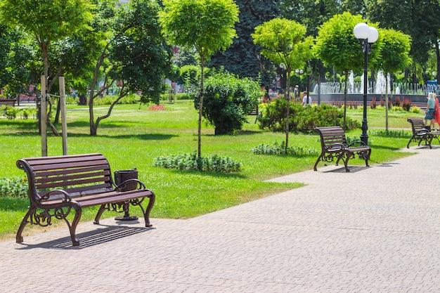 Aménagement paysager du parc de la ville avec des bancs et une fontaine.