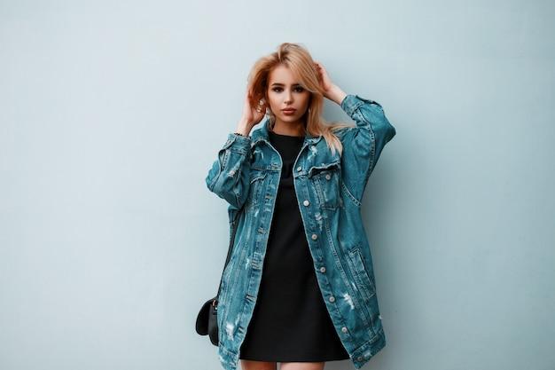 Américain glamour jeune blonde avec une veste en jean bleu à la mode dans une élégante robe noire avec un sac à main en cuir posant dans une pièce près d'un mur vintage
