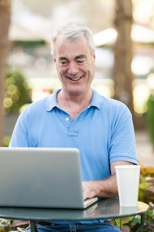 Américain senior homme avec ordinateur au parc
