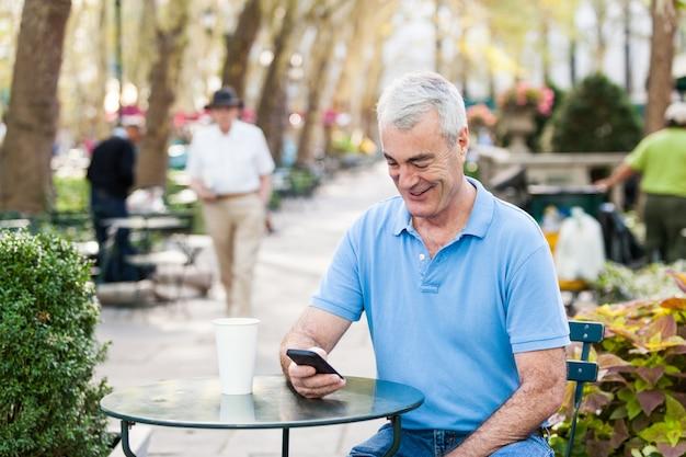 Américain senior homme avec téléphone portable au parc
