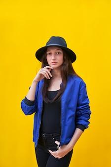 American flat young caucasian girl portrait in black hat et blue jacket, main sur le visage