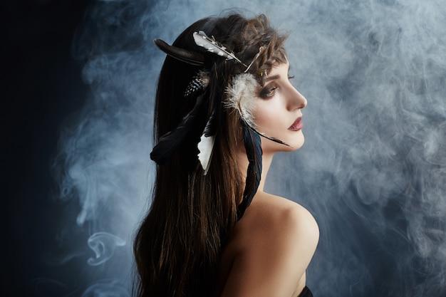 American indian girl avec des plumes dans le maquillage des cheveux