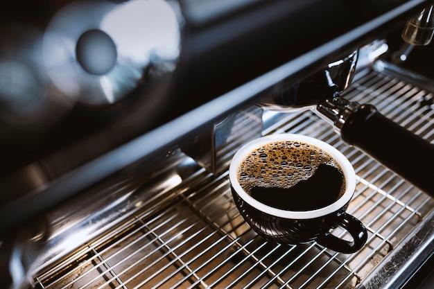 Americano chaud sur la machine à café du café avec flou artistique et lumière en arrière-plan