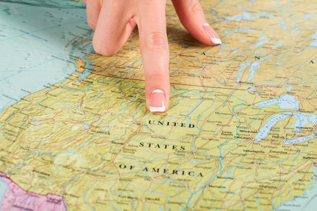 L'amérique sur la carte mondiale. le doigt de la fille pointe vers les états-unis. terre d'opportunité. l'un des plus grands pays.