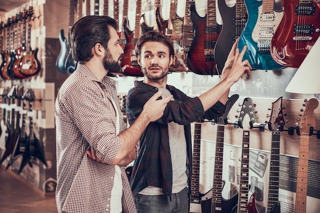 Un ami aide un ami à choisir la guitare électrique dans un magasin de musique