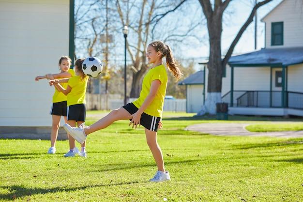 Ami filles adolescentes jouant au football football dans un parc