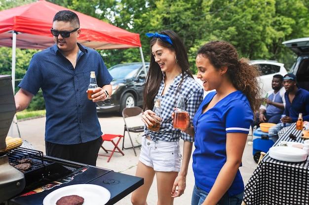 Ami grillant des hamburgers lors d'une fête de hayon