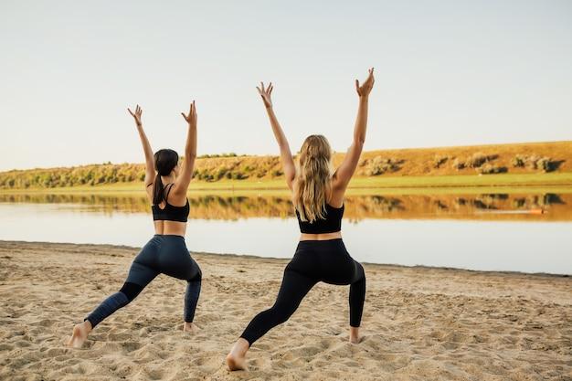 Ami de jeunes et belles filles faisant du yoga sur la plage de sable.