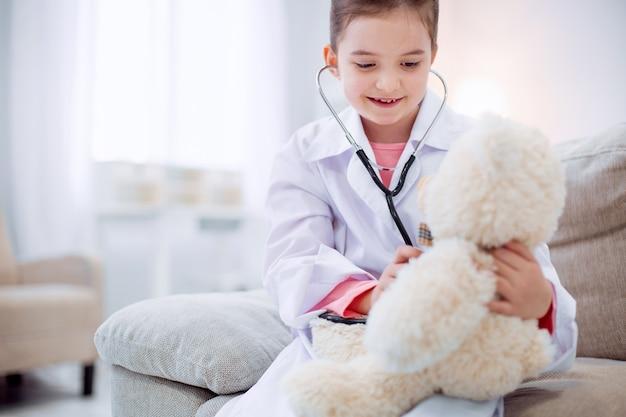 Ami en peluche. petite fille paisible aimable écoutant un ours en peluche tout en utilisant un stéthoscope et assis sur un canapé