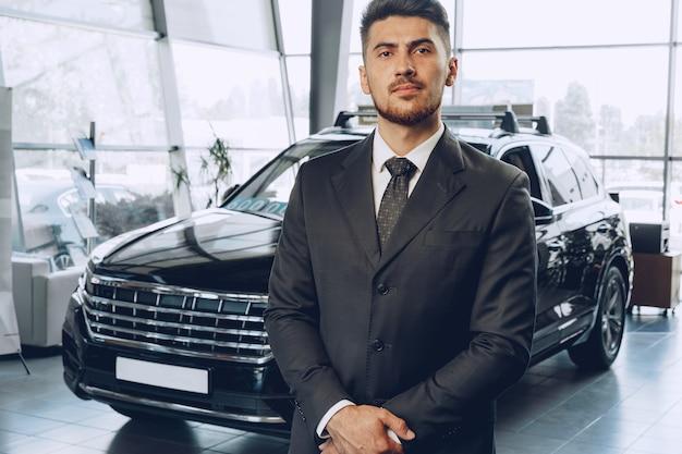 Amical beau vendeur de voiture homme debout dans un salon de voiture bouchent