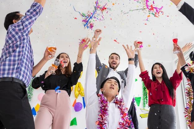Amical célébrant la tenue de flûtes de champagne tout en dansant à la fête sur la salle blanche.