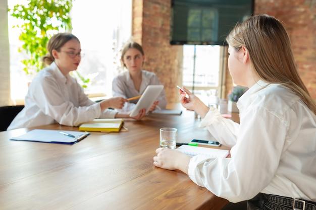 Amical. jeunes femmes de race blanche travaillant au bureau. réunion, donner des tâches, parler.