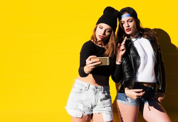 Amies adolescentes à l'extérieur font selfie sur un téléphone.