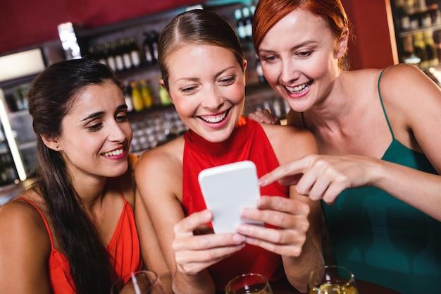 Amies à l'aide de téléphone portable tout en dégustant du vin