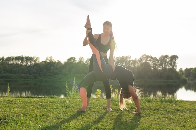 Amies appréciant le yoga relaxant en plein air dans le parc.