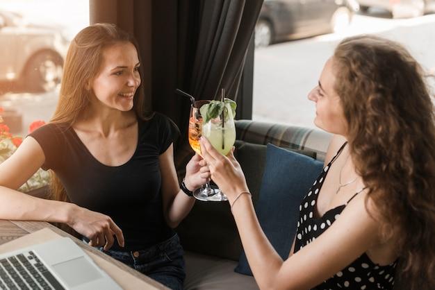 Amies assis dans un restaurant, verres de cocktails
