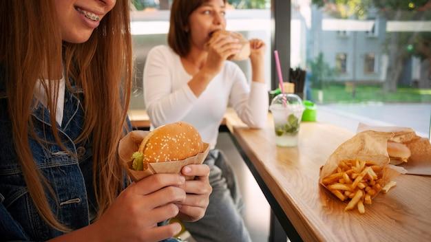 Amies ayant un hamburger ensemble