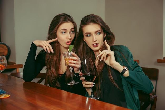 Amies ayant un verre au bar. ils sont assis à une table en bois avec des cocktails. ils portent des vêtements décontractés.