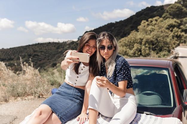 Amies branchées assis sur la voiture prenant selfie