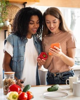 Amies dans la cuisine avec smartphone et légumes